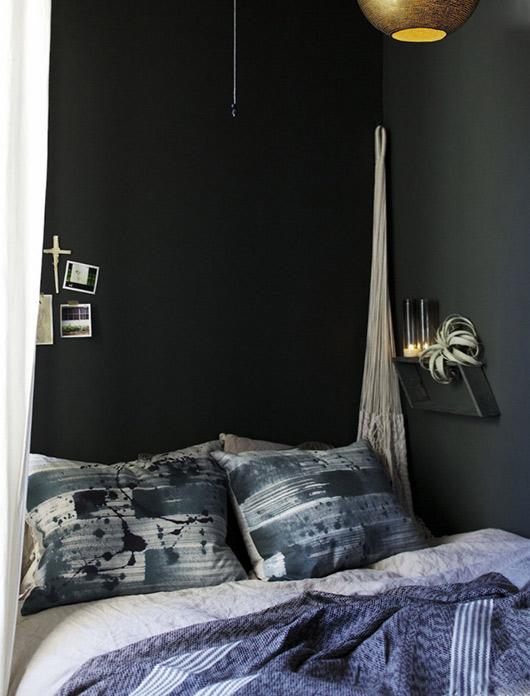 El dormitorio pintado en verde oscuro es muy acogedor.