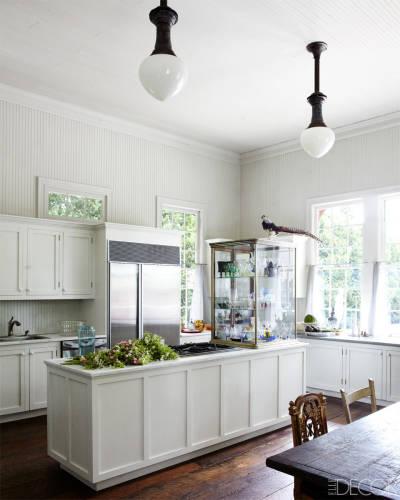 La cocina luminosa y abierta mezcla elementos de diferentes estilos, como las sillas y las lámparas de corte clásico.