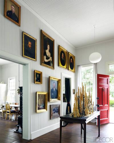 En la entrada de la vivienda se ha dispuesto una composición de pinturas de diferentes estilos, con marcos dorados que resaltan frente a la pared blanca.