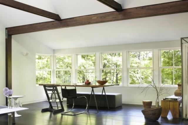 Vista del comedor con un gran ventanal y un banco corrido y tapizado como asiento.