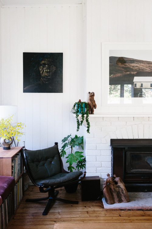 La zona de la chimenea, pintada de blanco con fotografías, plantas y mobiliario reciclado.