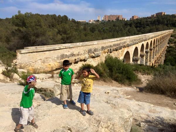 children exploring pont-del-diablo in spain