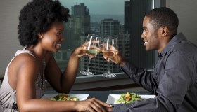 A couple toasting wine glasses on a dinner date