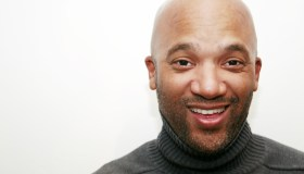 A smiling man with a bald head