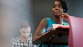 University student sitting at desk with hand on chin