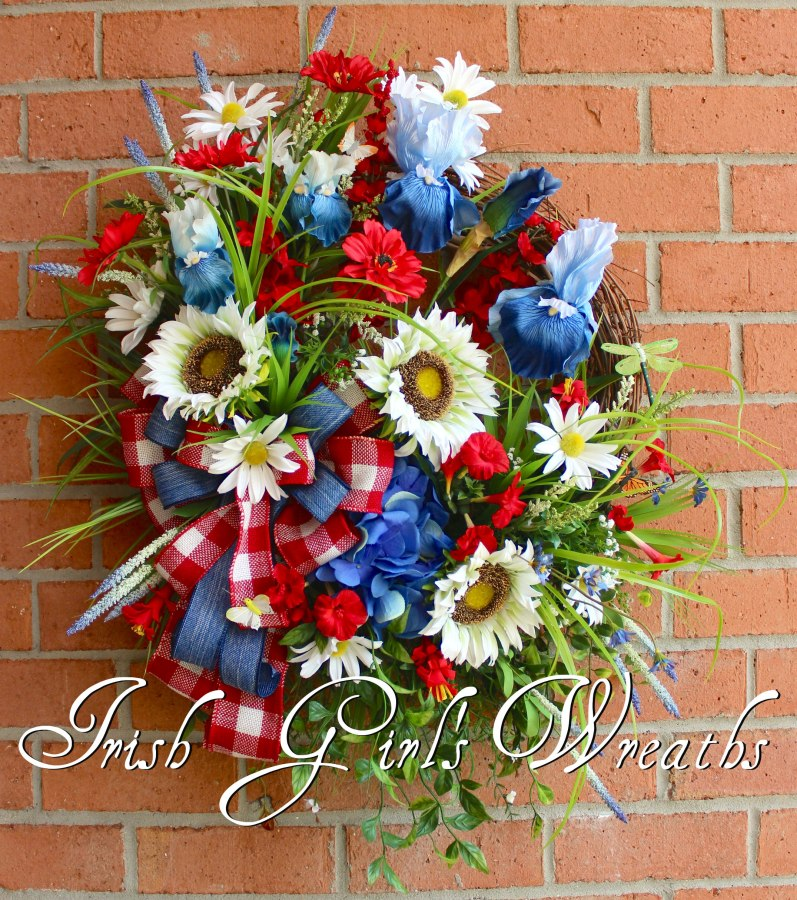 "Perfect from May-August, this large gorgeous American Patriotic Wreath includes: Iris, trumpet flowers, cosmos, Sunflowers, Delphiniums, Daisies, Hydrangea, and more! All perfectly tied together with a 3 ribbon red, white, and blue denim and burlap ribbon bow! Measures: 32""T x 25""W x 8""D"