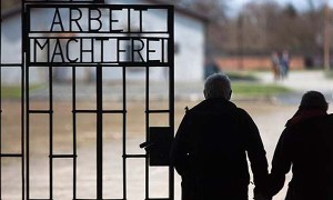 File- In this Jan. 27, 2012, file photo, a couple walks past the slogan 'Arbeit Macht Frei' (Work Sets You Free) at the main entrance of the Sachsenhausen Nazi concentration camp on the international Holocaust remembrance day in Oranienburg, Germany. An Associated Press investigation found dozens of suspected Nazi war criminals and SS guards collected millions of dollars in Social Security payments after being forced out of the United States.  (AP Photo/Markus Schreiber,File)