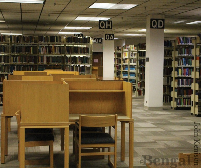 Table and chairs amid racks of books in the library.