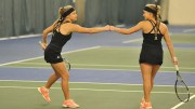 Two ISU women's tennis players fist-bump.