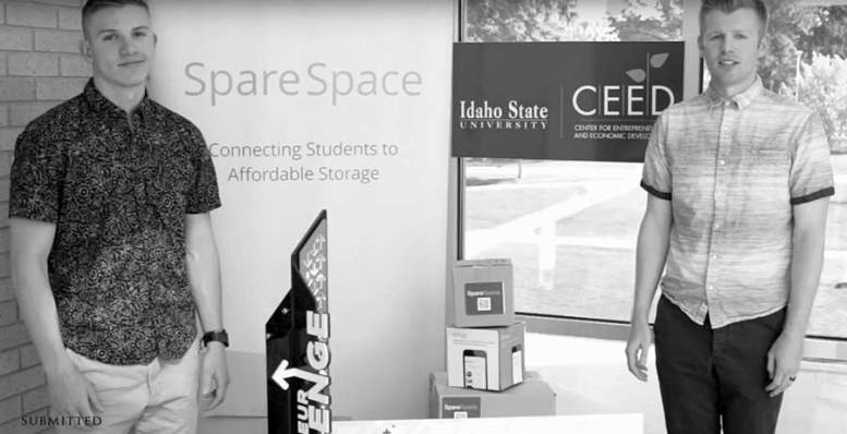 Two male students stand next to CEED program signs