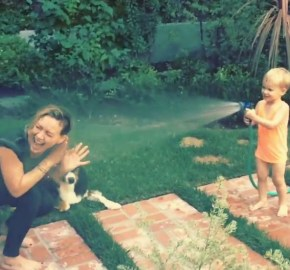 Luca spraying Hilary with a hose