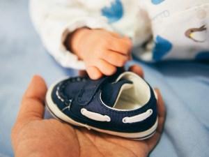 Man Holding Baby Shoe
