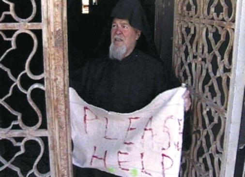 "A Greek Orthodox priest, held hostage by Palestinians who took refuge in the Church of the Nativity in Bethlehem, is holding a sign saying ""PLEASE HELP,"" April 2002. (Government Press Office)"