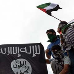 Kashmiri demonstrators hold up Palestinian flags and a flag of the Islamic State
