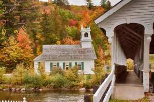 Fall foliage surrounds the Stark Covered Bridge is located on Northside Rd in Stark Village, Stark NH,  the Stark covered bridge crosses the Ammonoosuc River.