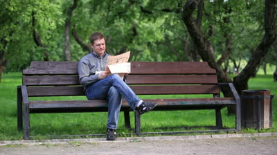 stock-footage-man-reads-a-newspaper-on-a-bench-in-the-park