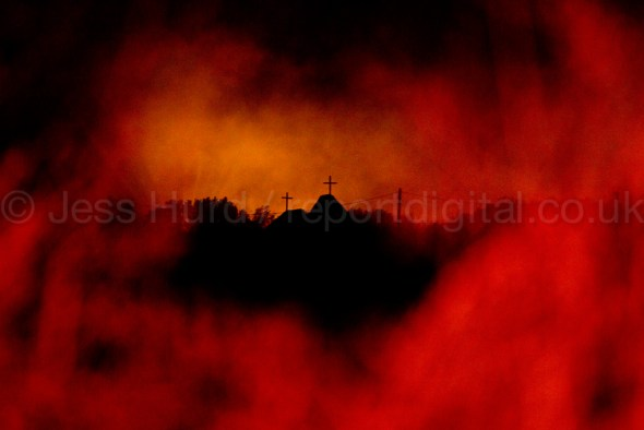 Smoke from fires illuminates the Eritrean Church after a tear gas battle with police in the Jungle refugee camp, Calais, France. © Jess Hurd/reportdigital.co.uk Tel: 01789-262151/07831-121483   info@reportdigital.co.uk   NUJ recommended terms & conditions apply. Moral rights asserted under Copyright Designs & Patents Act 1988. Credit is required. No part of this photo to be stored, reproduced, manipulated or transmitted by any means without permission.