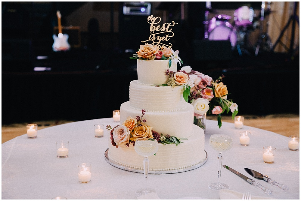 """Gold 'The Best is Yet to Come"""" cake topper on white cake with simple summer floral accents 