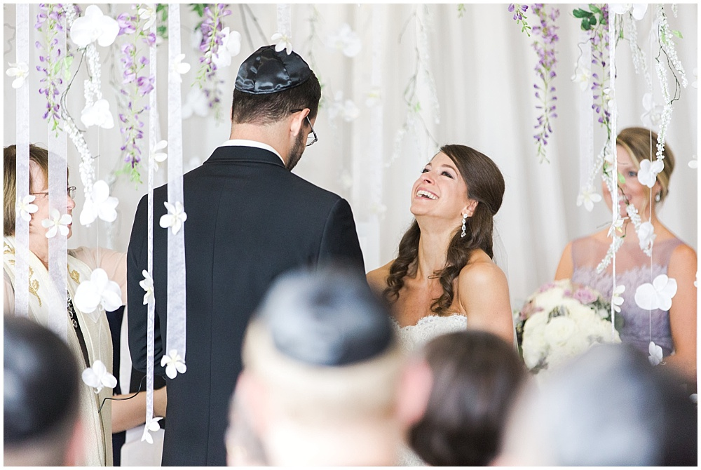 Bride and Groom under hanging purple and white floral chuppah | D'Amore Wedding by Ivan & Louise Images & Jessica Dum Wedding Coordination