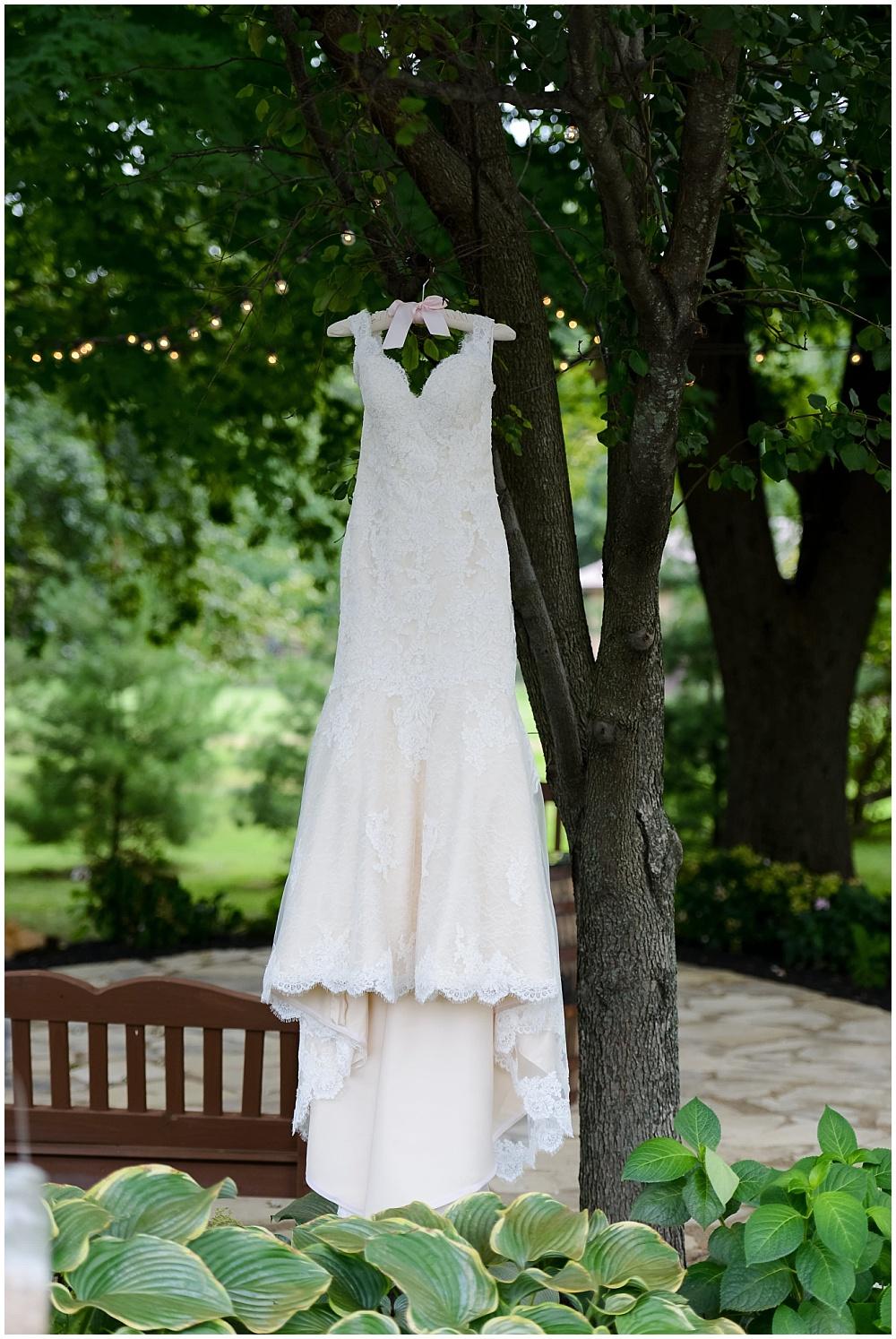 Lace wedding dress hanging from tree | Mustard Seed Gardens Wedding by Sara Ackermann Photography & Jessica Dum Wedding Coordination