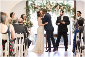 Bride and groom first kiss in front of floral ceremony arch   Laurel Hall wedding with Ivan & Louise Images + Jessica Dum Wedding Coordination