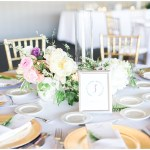 white on white wedding tablescape with gold chargers, gold chiavari chairs, hand lettered table numbers, fern sprig and menu tucked into napkin; Spring floral + gold wedding | Ivan & Louise Images | Jessica Dum Wedding Coordination