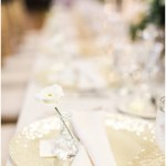 glass vanilla lace BBJ Linen chargers; individual bud vases with white flowers for each wedding guest; ivory horizontal napkin fold; bridal party head table; ; Scottish Rite Cathedral Indianapolis Wedding; neutral floral and greenery wedding| Ivan & Louise Images and Jessica Dum Wedding Coordination