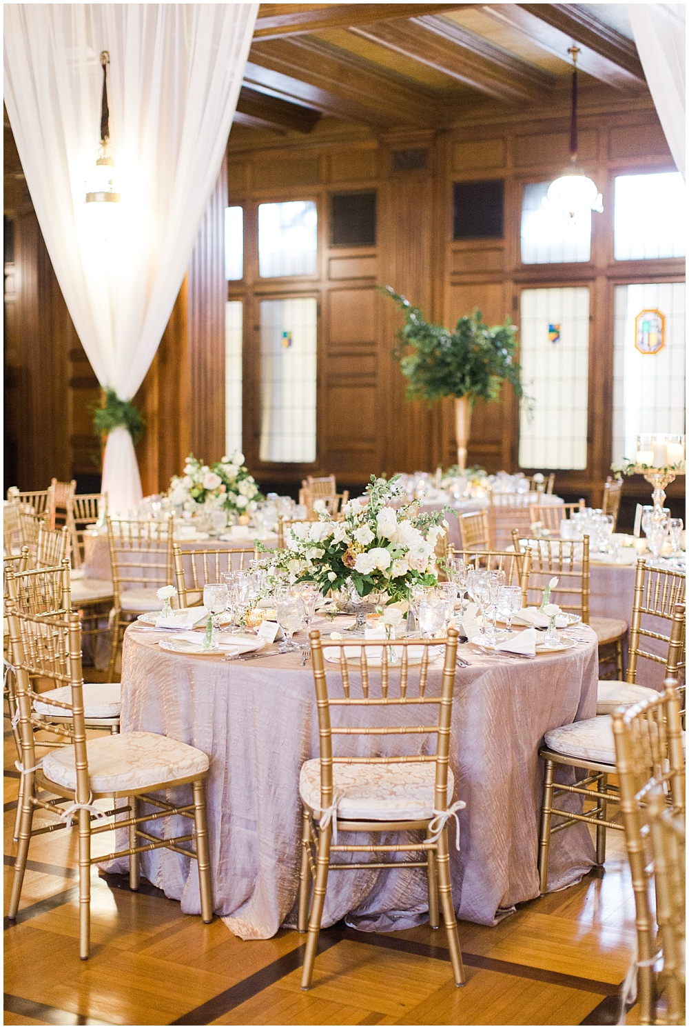 gold and ivory wedding tablescape; white drapes hanging with greenery tiebacks; Scottish Rite Cathedral Indianapolis Wedding; neutral floral and greenery wedding| Ivan & Louise Images and Jessica Dum Wedding Coordination