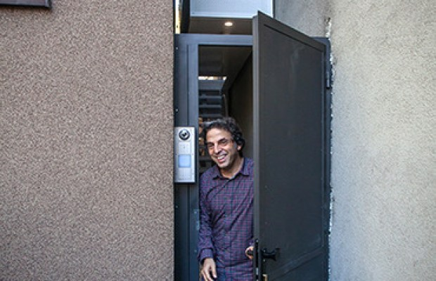 Etgar Keret squeezes through a front door (credit: Wojtek Radwanski)