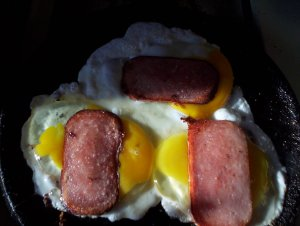 Crack three fresh eggs into the griddle, break the yolks, and top each with a thin slice of fried Spam.