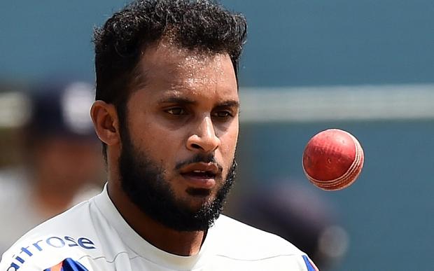 England's cricketer Adil Rashid tosses a