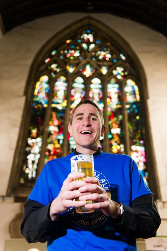 Rev Matt Woodcock with a pint in front of a large stained glass window