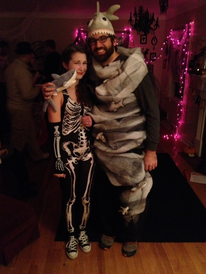 Woman dressed as skeleton poses with man dressed as a Sharknado at a Halloween party.