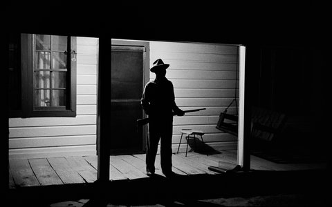The Rev. Joe Carter, expecting a visit from the Ku Klux Klan after he dared to register to vote, stood guard on his front porch in West Feliciana Parish, La., in 1964. (Credit: Bob Adelman via the New York Times)