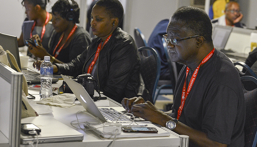 George Curry works on a story in the media center at the 2016 International AIDS Conference in Durban, South Africa. (Credit: Freddie Allen/AMG/BAI)