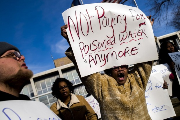 """Flint, Mich., resident Angela Hickmon, 56, calls for an end to paying water bills in the city until this """"man-made disaster"""" is figured out during a protest outside City Hall on Jan. 25, 2016, in downtown Flint, where residents tore up and burned their water bills. (Credit: Jake May/MLive.com)"""