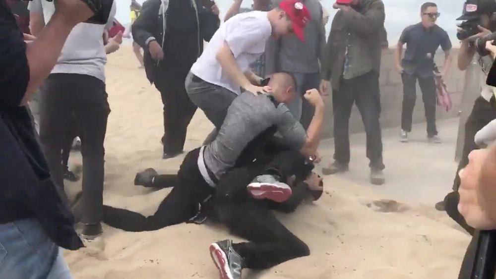Violence erupts at a Make America Great Again rally in Huntington Beach when a protester opposed to President Trump allegedly doused the organizer of the event with pepper spray and was immediately pummelled by a group of Trump supporters. (Credit: Cindy Carcamo/Los Angeles Times)
