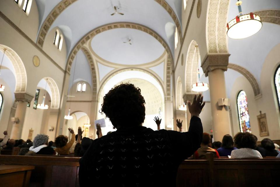 Marianne, the subject of a Boston Globe story, attends Mass in Mattapan, Mass. She works 40 hours a week and sends $50 to her eldest son, back in Haiti. (Credit: Pat Greenhouse/Boston Globe)