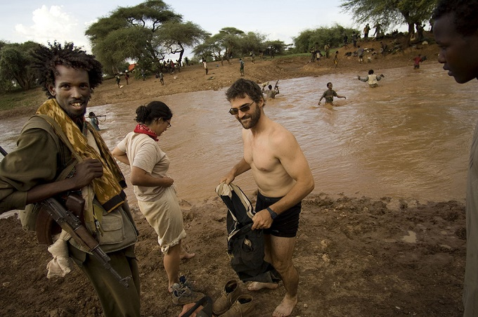 "New York Times correspondent Jeffrey Gettleman, in Somalia crossing a river with rebel fighter Commander Peacock, a ""heavily armed dreamer"" (Credit: Kenya Buzz)"