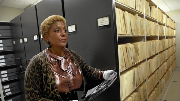 Linda Johnson Rice handles some of the photos in the archives at Johnson Publishing in 2015. (Credit: Nancy Stone /Chicago Tribune)