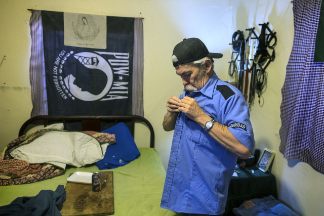 """Carlos Torres, 61, a deported Army veteran, puts on his """"seguridad"""" (security) uniform before going to work at a maquila at his home in Reynosa, Mexico. (Credit: Rodolfo Gonzalez/Austin Amercian-Statesman)"""