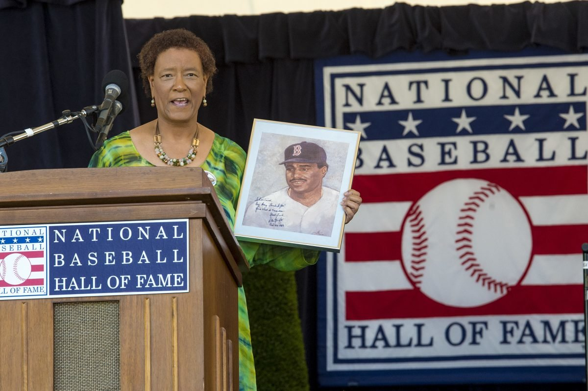 Former Philadelphia Inquirer sports columnist Claire Smith holds up a painting of former player Don Baylor — painted by her father — as she gives her acceptance speech after receiving the J.G.Taylor Spink Award from the Baseball Hall of Fame. (Credit: Clem Murray/Philadelphia Inquirer)