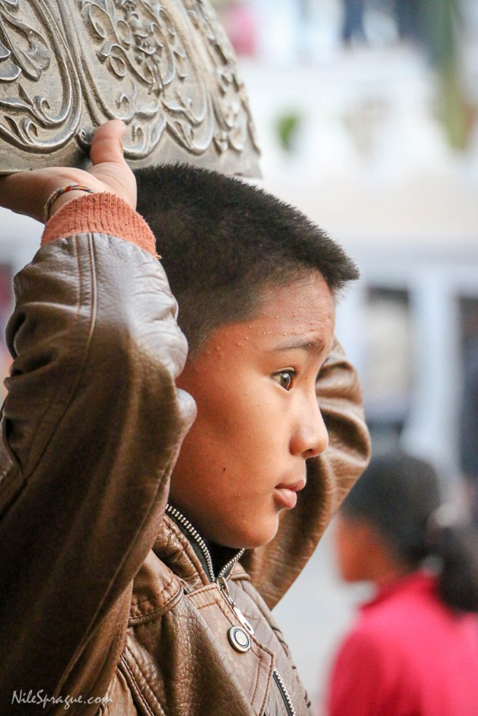 Boy standing under a huge bell on the perimeter of the stupa at Boudhanath. Each evening, hundreds of people gather at the stupa to walk kora, circumambulating the stupa in a clockwise direction as they say prayers, turn prayer wheels, and interact with one another.