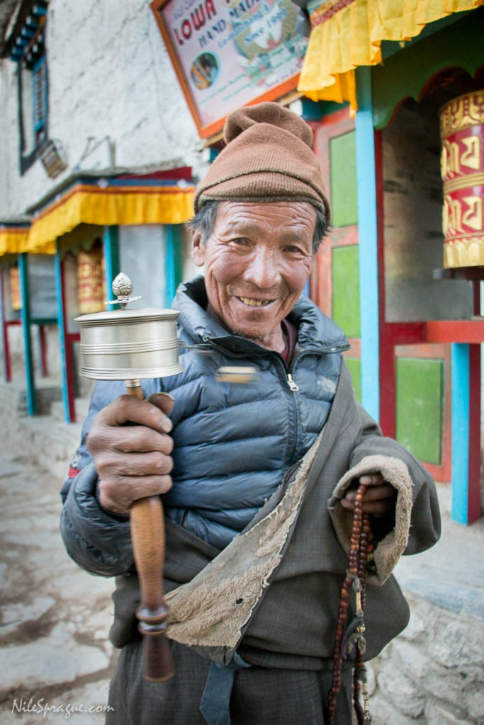 Tibetan man spinning prayer wheel, Lo Manthang, Upper Mustang. Late in the afternoon each day, most of the residents of the small capital city would turn out to walk kora, circumambulating the perimeter of the city in small groups in a clockwise direction, saying prayers, turning prayer wheels, and chatting.