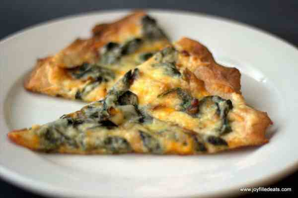 This low carb White Spinach Pizza is topped with a creamy garlic sauce, four cheeses, sauteed onions, & spinach. It is gluten free, grain free, & THM S.