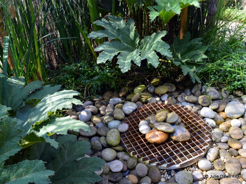 Pebble fountain and large green leaves