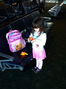 little girl in an airport with a backpack