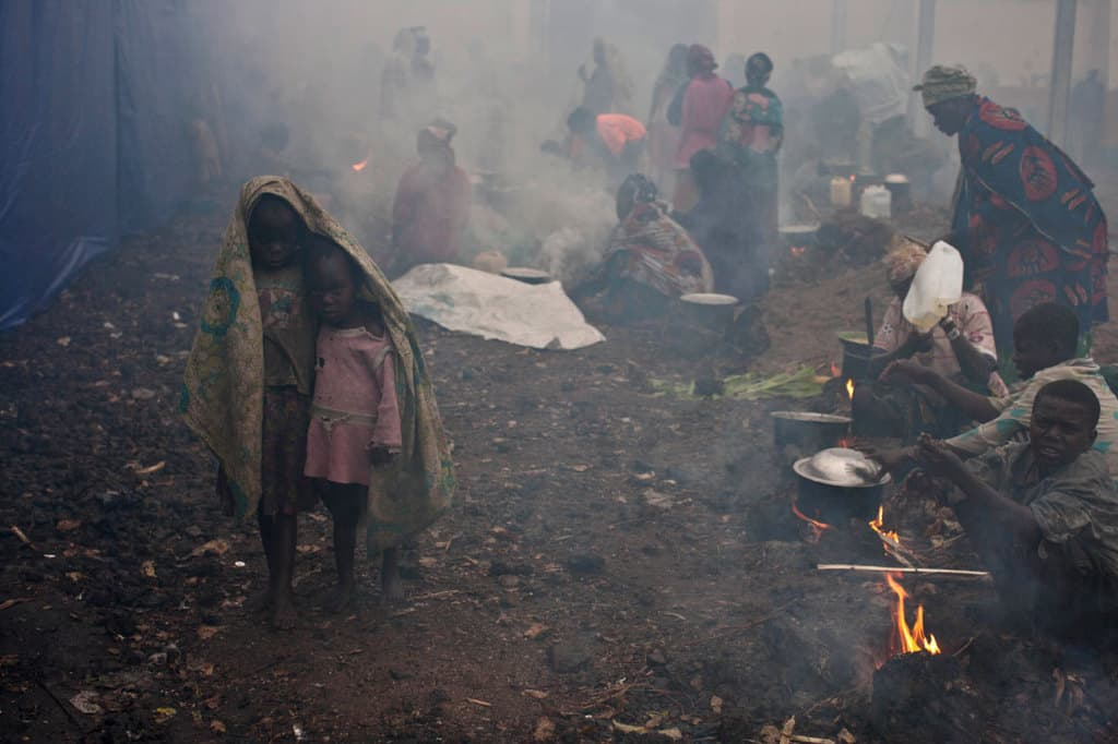 A brother and sister who have been displaced by recent fighting between M23 rebels and Congolese Government soldiers shelter under some material. Kate Holt.