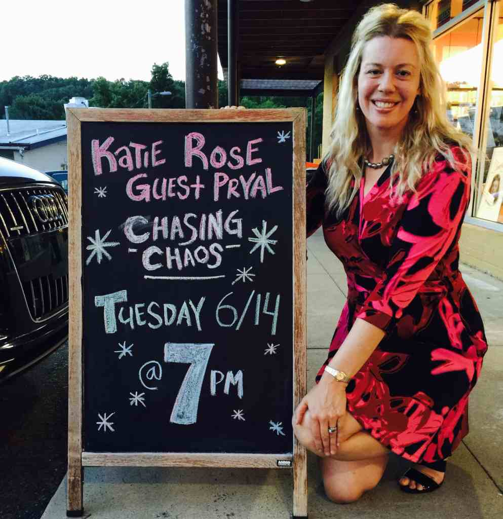 Alt Text: Photograph of author Katie Rose Guest Pryal kneeling next to chalkboard sign in front of Flyleaf Books. The sign reads: Katie Rose Guest Pryal, CHASING CHAOS, Tuesday, 6/14 @ 7pm
