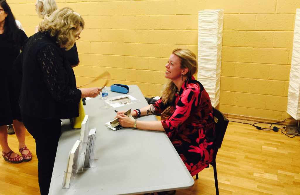 Alt Text: Photograph of author Katie Rose Guest Pryal signing books at her launch party for Chasing Chaos. She is sitting behind a gray table wearing a red and black dress.